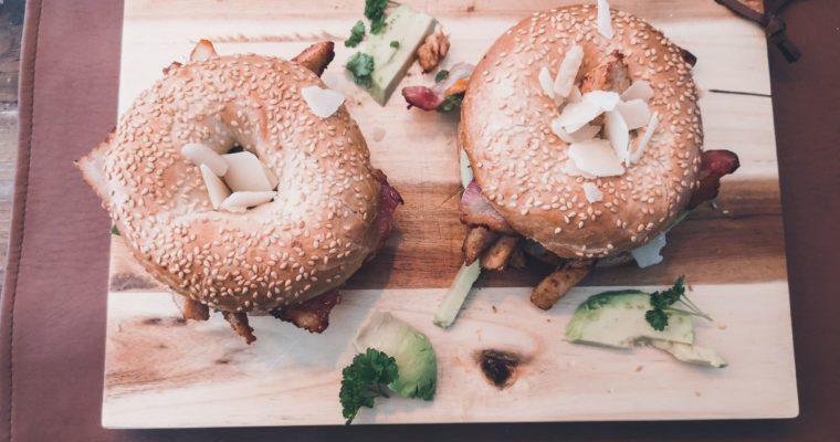 Rijkelijk belegde bagel met kip, spek en avocado
